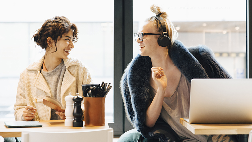 Smiling customers talking while sitting against window in coffee shop