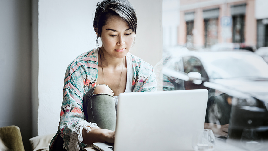 Young Woman Working On Laptop In Cafe Window